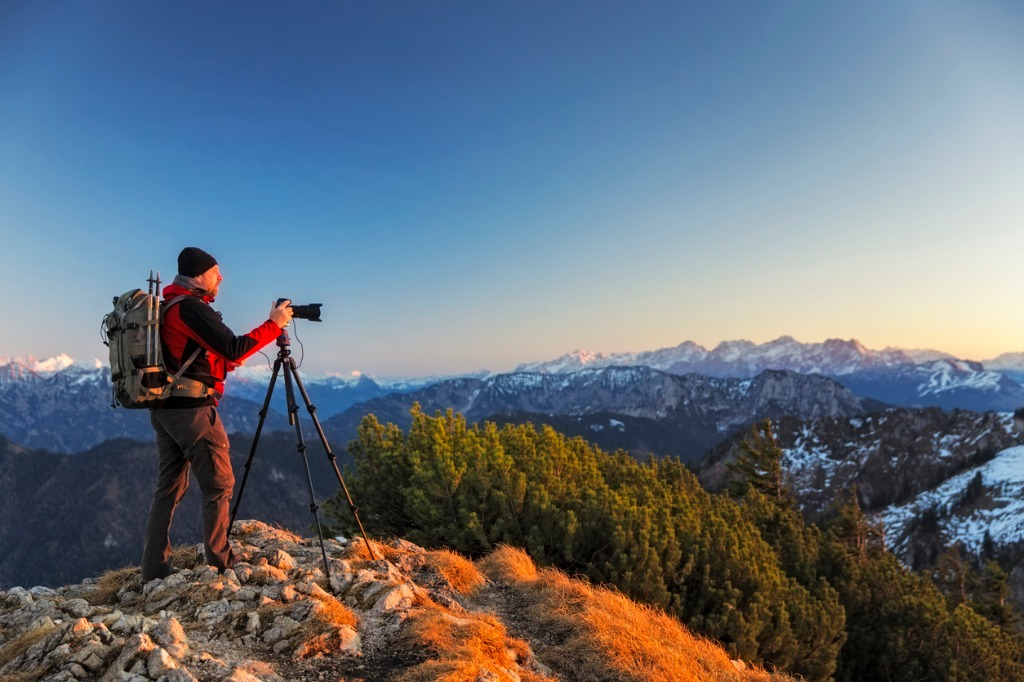 nature photographer with tripod an backpack in the alps picture id598829240