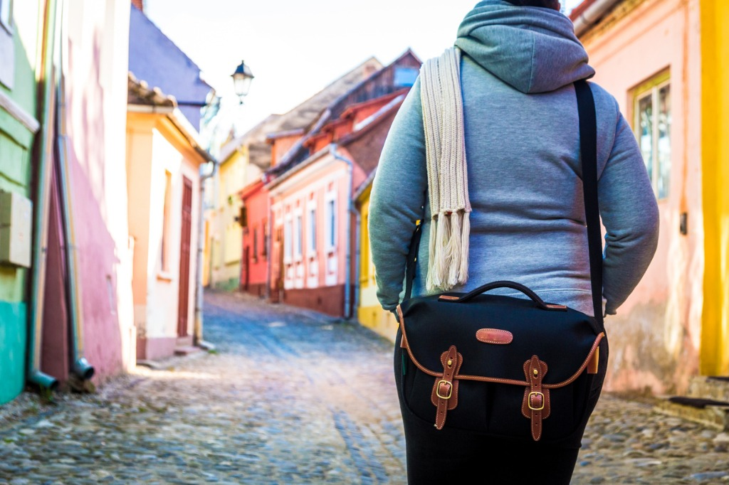 rear view of female traveler wearing black shoulder bag with houses picture id681154668