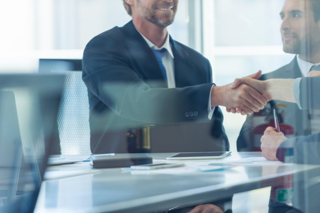 businessmen shaking hands at the board room table picture id859896862 image