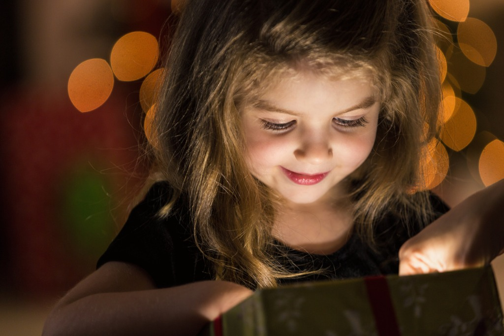 curious girl peeks inside a christmas present picture id580120952 image