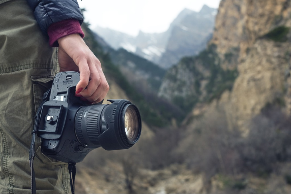 female hand holds a camera against a mountain landscape picture id866954210 image