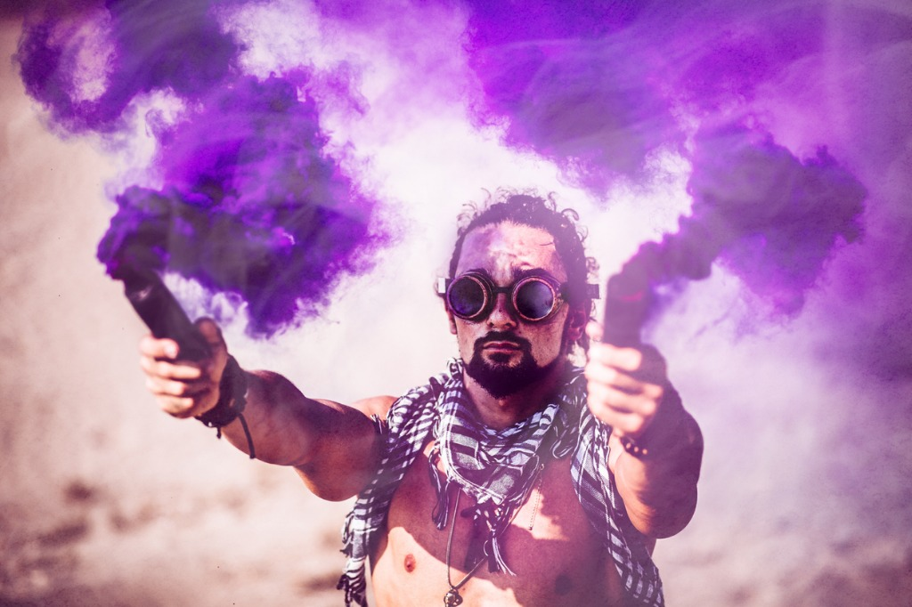 man with futuristic steampunk goggles and smoke bombs in desert picture id874099474 image