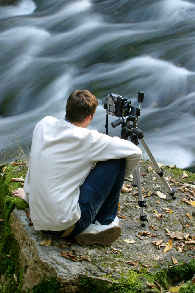 photographer sitting by river with camera and tripod picture id108128410