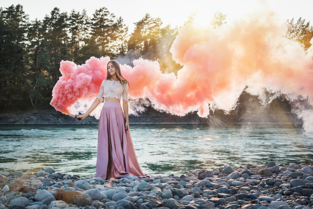 girl with a smoke bomb on the bank of a mountain river with pink and picture id962713380 image